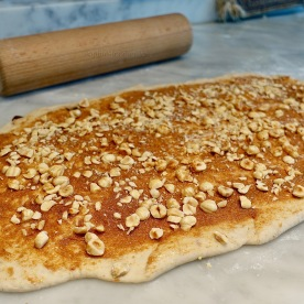 Pushing chopped hazelnuts into the dough!